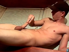 Masturbating boy cums on a glass table
